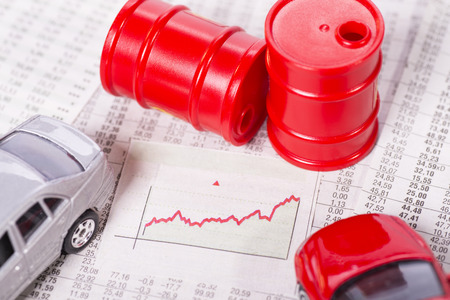 Diagram with on ascending curve surrounded by cars and oil barrels Stock Photo