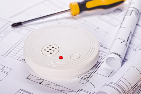 Smoke detector lying on blueprints with screwdriver in the background