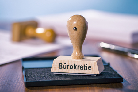 inkpad: A stamp with the inscription bureaucracy stands on a desk.