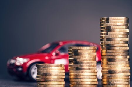 Rising stack of coins with red car in the background