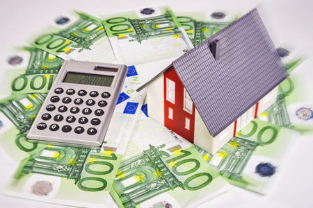 mortgaging: House with euro money and calculator.