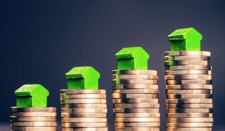 mortgaging: Small green houses standing on stacks of coins.