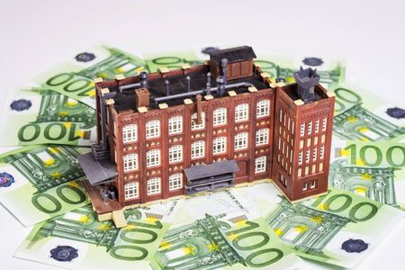 hedging: Factory building is surrounded by euro banknotes. Stock Photo