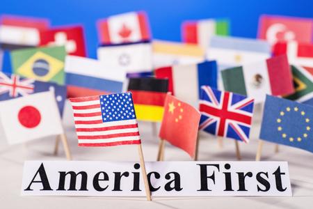 アメリカの国旗は、アメリカ最初のスローガンと他の国の多くのフラグの前にあります。 写真素材