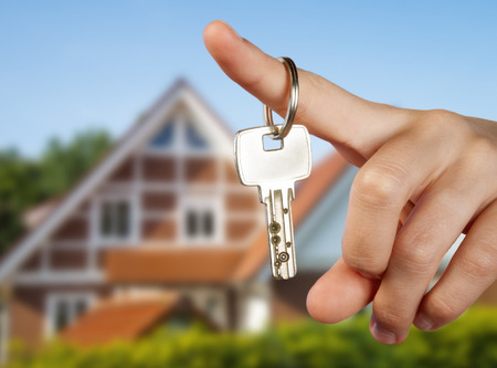 Hand holding a key in front of a country house Stock Photo