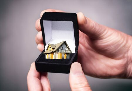 Hand holding jewellery box with house Stock Photo