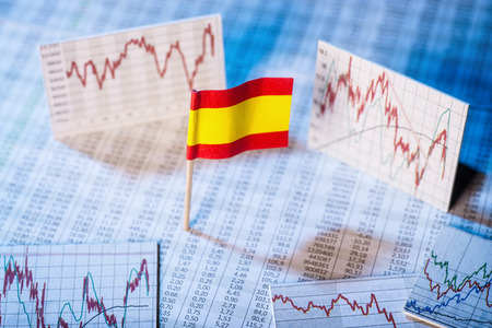 Spanish flag with rate tables and graphs for economic development.
