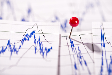 Diagrams show stock prices, one is marked with a pin. Фото со стока
