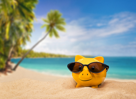 バック グラウンドで熱帯のビーチとサングラスと黄色い貯金箱