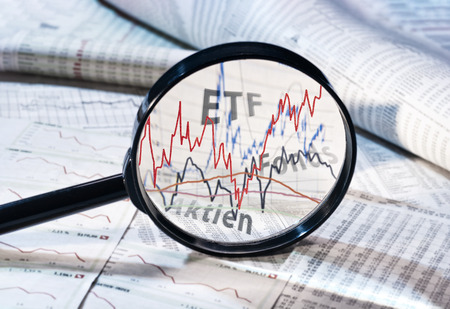 Magnifying glass shows the courses of ETF, funds and shares 스톡 콘텐츠