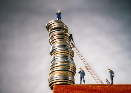 Een hoge stapel munten en bankiers op afgrond
