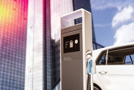 E-car at a charging station in front of a skyscraper