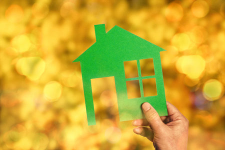 Green silhouette of a house in front of a blurred background in warm colors with bokeh