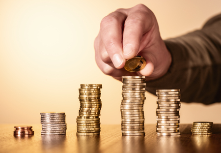 Several stacks of coins. On one pile another coin is placed. Stock Photo