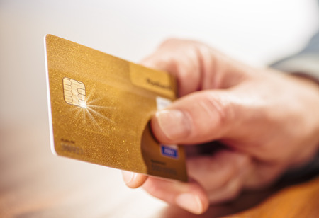Closeup of a hand with a golden credit card Imagens - 91499859