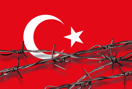 Barbed wire with shadow in front of a Turkish flag