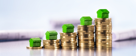 Small green houses stand on stacks of coins with blueprints in the background. Stock Photo