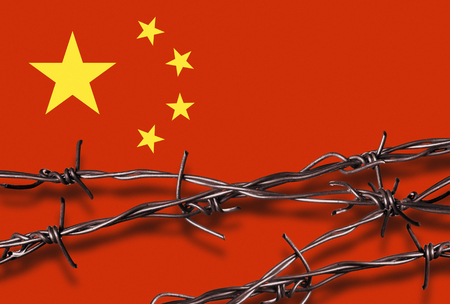Barbed wire with shadow in front of a Chinese flag Stock Photo