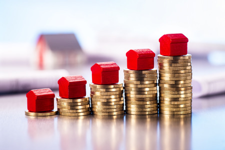 Kleine rode huizen die zich op stapels muntstukken met blauwdrukken en architecturaal model op de achtergrond bevinden. Stockfoto