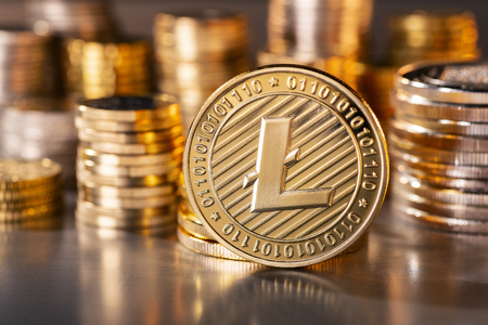 Coin of the crypto currency Litecoin with several stacks of coins in the background Banque d'images - 100147331