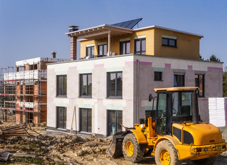 A new building next to a shell in a construction area with a wheel loader in the foreground Banque d'images - 100164774