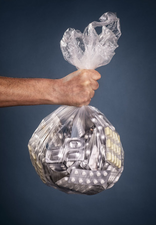 Hand holds a plastic bag with many medicines Banque d'images - 106192878
