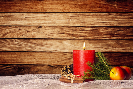 Red candle with christmas decoration in front of wooden wall with copy space Banque d'images - 110031541