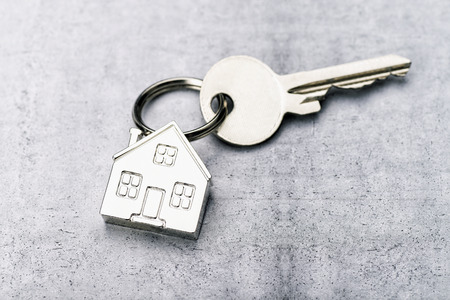 Key with house as a key fob on a concrete background