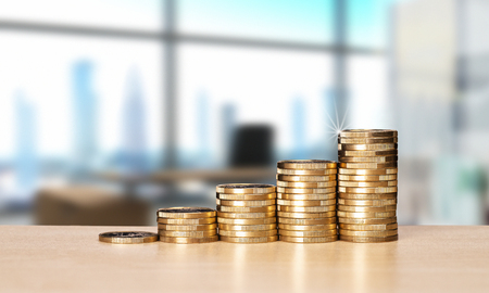 Rising stacks of coins on the desk in an office with a skyline in the background. Banque d'images - 110031545