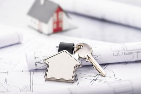 Baupläne und Haus als Schlüsselanhänger mit Architekturmodell im Hintergrund