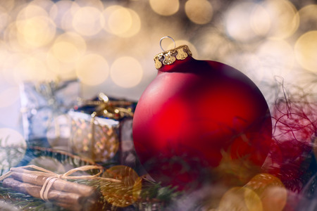 Red bauble and Christmas decoration with fir branches and bokeh
