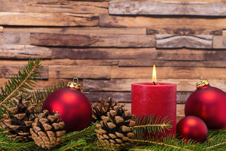 Christmas decoration with candle, christmas tree balls, fir branches and pine cones in front of wood background Banque d'images - 110031596