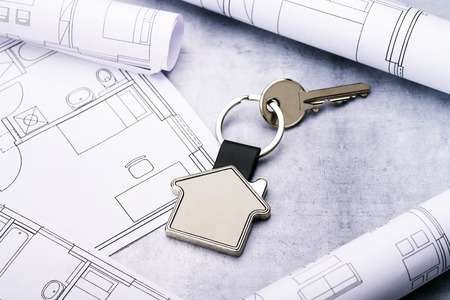Key with house as key fob and blueprints on a concrete background Banque d'images - 110031599