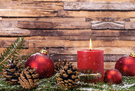 Christmas decoration with candle, Christmas tree balls, fir branches and pine cones in the snow in front of wood background Banque d'images - 110031604