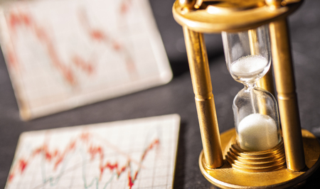Sand trickles through an hourglass with graphics showing stock prices in the background. Symbol for the time factor at the investment. Stock Photo