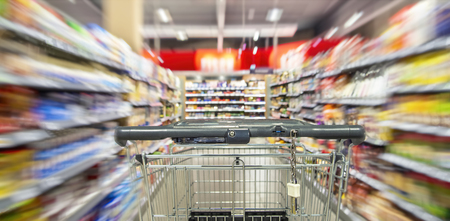 An empty shopping cart between shelf rows in the supermarket with motion blur.
