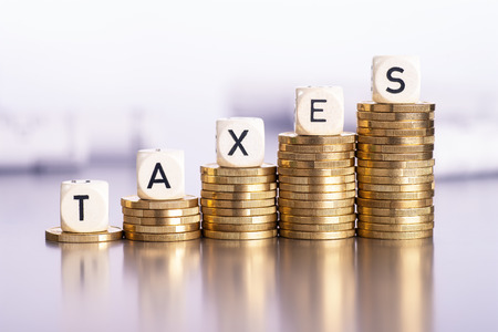 Rising stacks of coins with the word taxes