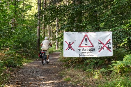Cyclist on a forest path next to a sign for forestry work