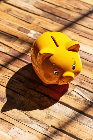 A yellow piggy bank stands on a wooden floor and casts a strong shadow Stock fotó
