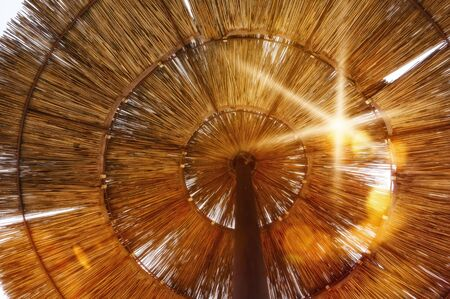 View from below through a parasol made of straw to the sun