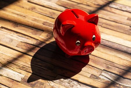 A red piggy bank stands on a wooden floor and casts a strong shadow