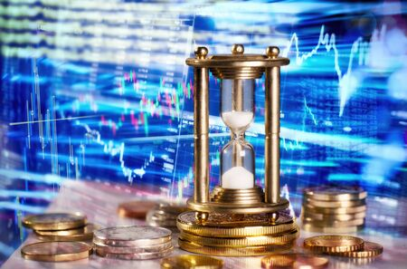 Computer trading on international financial markets with an hourglass in the foreground Stock Photo