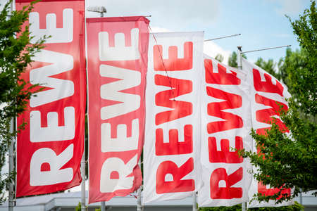 Flags with the logo of the supermarkets of the grocer Rewe