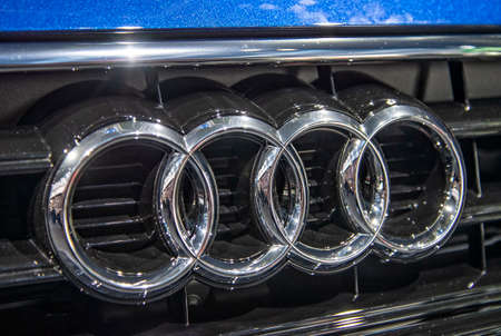 The logo of Audi on a blue car of this brand Editorial