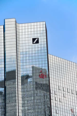 Deutsche Bank headquarters in Frankfurt with logo and reflection of the Sparkassen logo in the facade Editorial