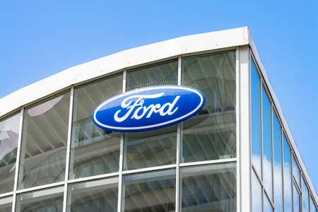 Ford logo on the glass facade of a car dealership