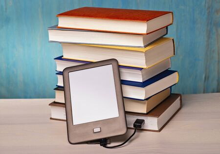 An e-book reader is connected to a stack of books via USB cable