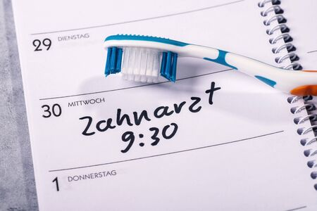 Calendar on which a toothbrush is placed and in which an appointment for a visit to the dentist is entered Standard-Bild