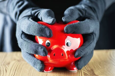 Hands in black gloves clasp a red piggy bank Standard-Bild