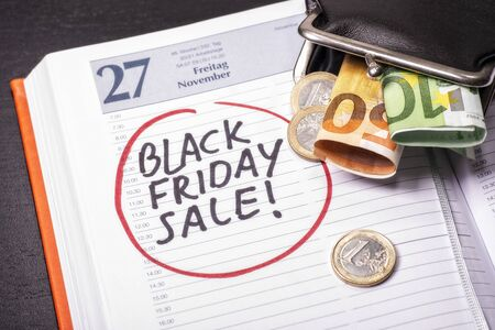 Date for Black Friday Sale in a calendar on which there are coins and banknotes Standard-Bild